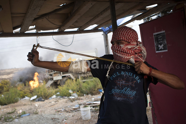 A Palestinian protester uses a sling shot to throw stones at Israeli security forces during clashes near the Jewish settlement of Bet El, near the West Bank city of Ramallah, on October 13, 2015. A wave of stabbings that hit Israel, Jerusalem and the West Bank this month along with violent protests in annexed east Jerusalem and the occupied West Bank, has led to warnings that a full-scale Palestinian uprising, or third intifada, could erupt. The unrest has also spread to the Gaza Strip, with clashes along the border in recent days leaving nine Palestinians dead from Israeli fire. Photo by Shadi Hatem
