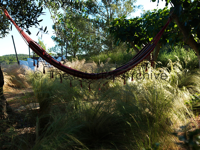 A tasselled hammock hangs in a shady spot in the garden