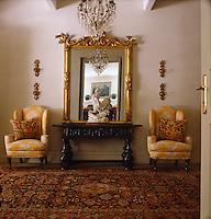 A pair of yellow upholstered wing-backed armchairs flanks a console table and a gilt-framed mirror in the hall