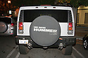 A rear view of a gas guzzling Hummer H2 with a custom license plate '01 MPG ( One Mile Per Gallon). The license plate underestimates the vehicles range by about 12 miles per gallon.