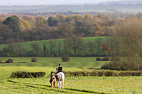 Mother and daughter ride together through rolling hills and fields in Oxfordshire, The Cotswolds, UK