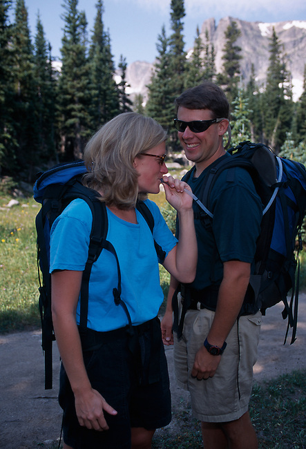 Couple sharing drink of water after summer hike, Rocky Mtns, CO