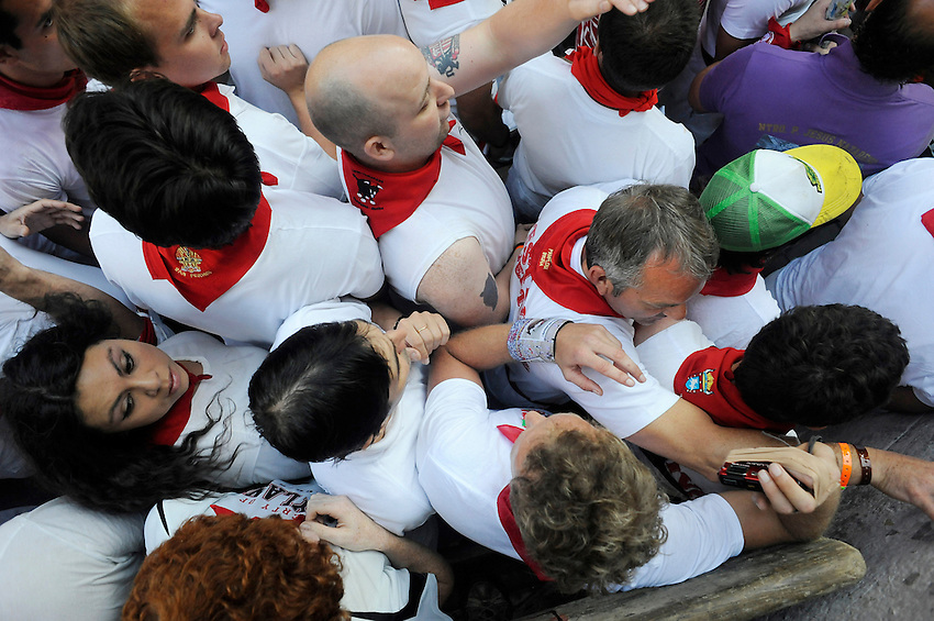 Participants huddle during the third San Fermin Festival´s running of the bulls, on July 9, 2013, in Pamplona, Basque Country. A leading ox has dead into the bullring during the third running of the bulls. On each day of the eight San Fermin festival days six bulls are released at 8:00 a.m. (0600 GMT) to run from their corral through the narrow, cobbled streets of the old navarre town over an 850-meter (yard) course. Ahead of them are the runners, who try to stay close to the bulls without falling over or being gored. (Ander Gillenea / Bostok Photo)