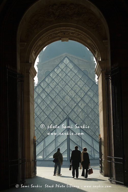 The Louvre Pyramid, seen from a grand archway, Paris, France.