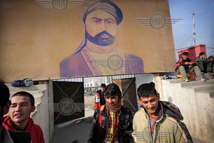 Youths gather in a sports stadium in Kabul. The stadium is decorated with portraits of kings, former rulers and people who played an important role in the cultural history of Afghanistan.
