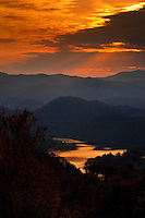 A setting sun creates a dramatic sky over the mountains surrounding Watauga Lake in Butler, Tennessee.