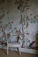A painted antique chair stands in front of a wall papered in historic listed floral pattern wallpaper
