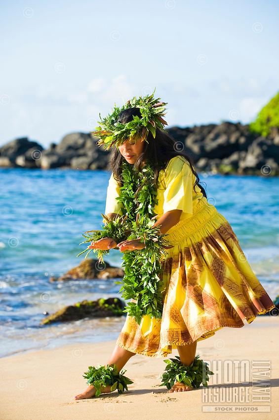 Kahiko hula dancer in yellow costumr with maile lei.
