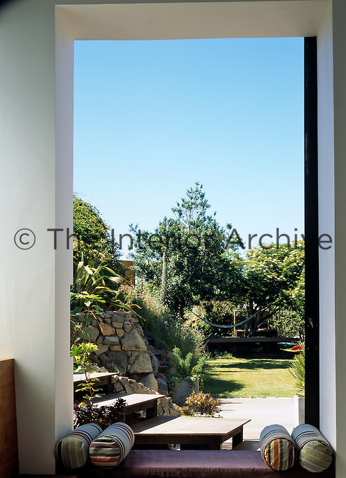 The window seat at the foot of a large sliding glass door is the perfect spot from which to enjoy views of the garden