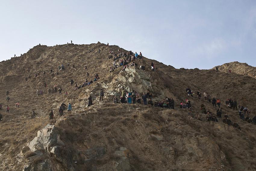 Des dizaines de personnes se sont perchées sur la colline surplombant le monastère de Labrang pour assister à la procession qui va voir les moines transporter en chantant une immense Tangkha (tapisserie) de Bouddha pour la déployer sur une autre colline au sud.