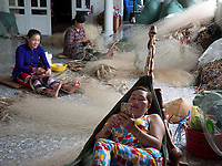 Women mending fishing Nets while the man are out fishing, this is mainly a family task. Bac Lieu, Vietnam