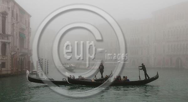 Venice-Italy - January 16, 2011 -- Gondolieri / gondoliers on tour with tourists on Grand Canal / Canal Grande in the early morning winter mist, gondola -- tourism, infrastructure, transport, water -- Photo: Horst Wagner / eup-images