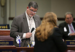 Nevada Assemblyman James Oscarson, R-Pahrump, answers a question from Assemblywoman Maggie Carlton, D-Las Vegas, during Assembly floor discussion at the Legislative Building in Carson City, Nev., on Monday, April 6, 2015. <br /> Photo by Cathleen Allison