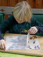 Kinder basteln ein Fensterbild mit Blüten, Junge klebt zweites Pergamentpapier auf das mit Blüten beklebte Pergamentpapier