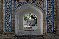 Detail of a woman sitting on a bench in the courtyard of the Memorial of Baha Ad-Din Naqshband, died 1389, patron of Bukhara, seen through the richly decorated archway to the tomb, Bukhara, Uzbekistan, on July 12, 2010, in the afternoon. The construction of the whole complex took over five centuries. Bukhara, a city on the Silk Route is about 2500 years old. Its long history is displayed both through the impressive monuments and the overall town planning and architecture.