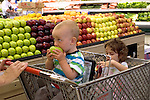 Berkeley CA Siblings one and three-years-old sampling apples while doing grocery shopping with mother