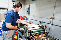 "Mississippi State senior art/graphic design major Mitchell S. ""Mitch"" Phillips of Brandon works on a letterpress project in Assistant Professor Suzanne Powney's printing class. At Mississippi State, the letterpress is specific to the graphic design program. Letterpresses are used to print textured designs, generally on invitations or posters, and these kinds of prints were common throughout the country until the 1960s when the industry moved to offset printing."