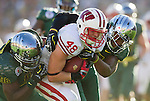 Oregon Ducks defensive lineman Dion Jordan (96) and linebacker Michael Clay (46) tackle Wisconsin Badgers tight end Jacob Pedersen during the 2012 Rose Bowl NCAA football game in Pasadena, California on January 2, 2012. The Ducks won 45-38. (Photo by David Stluka)