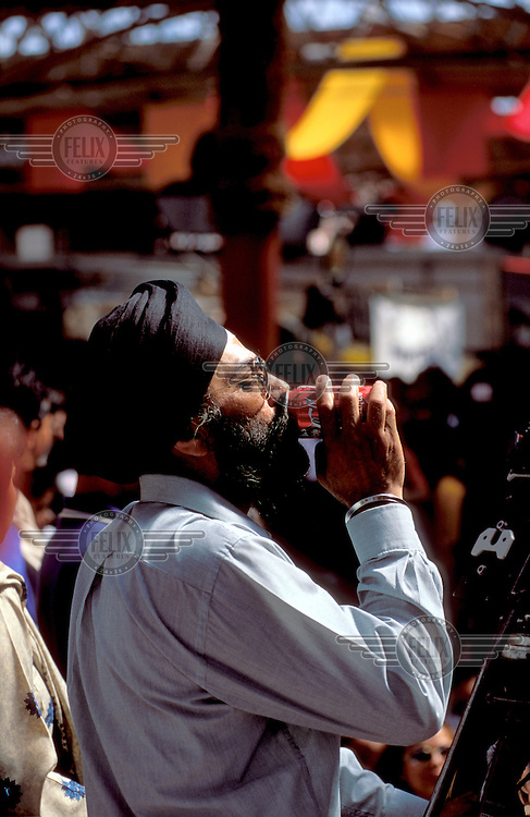 © JC Tordai / Panos Pictures..London, England, UK..Sikh man enjoying a can of Coca Cola in Spitalfields market.