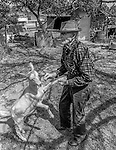 "December 1971:  Modesto, California—Dad Walkling— Dad plays with kid goat in his back yard.  I first met Orlando ""Dad"" Walkling at his house in the airport district of Modesto just before his 104th birthday.  Walkling was born in Indian Territory January 2, 1868, near a town now called McAlester, Oklahoma.  His mother was Shawnee and his father, whom he didn't remember, was an Englishman named Orlando.  He later used the name Walkling instead of his Indian name of Skipocase.  On September 16, 1893, Skipocase O. Walkling, then 25 years old, was among thousands of settlers who rode into the Cherokee Strip Land Run of Oklahoma to make a free land claim.  Walkling told of how he rode into the 226-mile long ""Strip"" to claim 160 acres.  ""There were thousands of men who waited at the line until noon that day.  The army gun was fired and chaos broke out. Every man carried a gun. There was no law, no sheriff, nothing.  People had to fight for their claim even though they were first.""  Walkling made a claim, but later gave it up when he had a chance to farm a piece of land in Noble County, Oklahoma.  He cleared the land with six yoke of oxen and planted peach orchards.  He and his first wife ran a combination grocery store and hotel there.  He had nearly 1,000 trees and began a cannery to process the crops.  ""One day when the train came in a woman dressed like a Salvation Army woman handed me a bundle as I stood on the ramp, then she jumped back into the train.  I opened it and there was a pair of twins, a boy and a girl,"" Walkling said.  He and his wife did not have children, so they adopted the twins legally and raised them.  He said they raised six others but did not adopt them.  He came to Modesto in 1944 at 76 years of age and went to work for a meat firm before he opened a poultry store.  After that store closed, he made bullwhips and wove rope for truckers at his home.  In 1968, Dad Walking, then 100 years old, visited Oklahoma for the 75th anniversary of the"