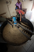 Workers operate a coffee roasting machine in a coffee roasting plant in Dili, Timor-Leste on Thursday, Oct. 27th, 2011.  The coffee industry is Timor's biggest employer and second largest export only to oil.  Photographer: Daniel J. Groshong/The Hummingfish Foundation