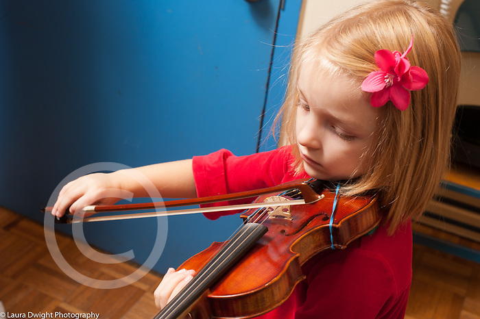 Education elementary Kindergarten music enrichment female student playing the violin in private music lesson