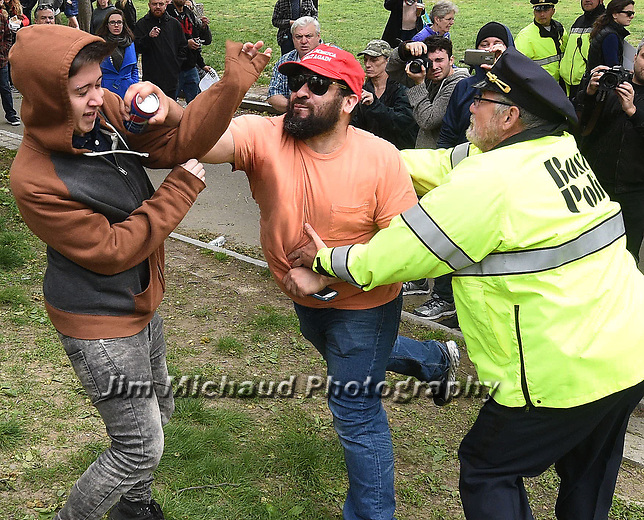 (Boston MA 05/13/17) A Trump supporter wearing a Make America Great Again cap, right, takes a swing at a counter protester who rushed him after the Trump supporter used a Pepsi to taunt the anti-Trump protesters mimicking the Pepsi commercial with racial overtones, both were arrested, during a large demonstration on 6 different militias and a counter protest, Saturday, May 13, 2017, on the Boston Common. . Herald Photo by Jim Michaud