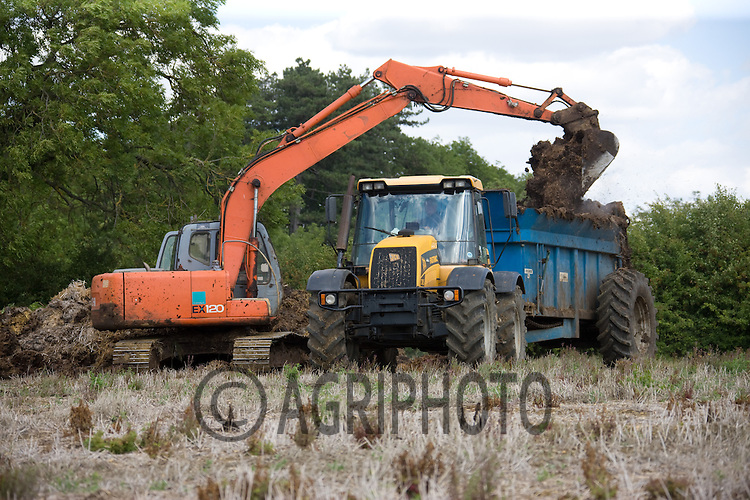 Contractors using a digger to load the spreader whilst spreading farm yard manure on oilseed rape stubble in Lincolnshire.Picture Tim Scrivener date taken 9th August  2011 .mobile 07850 303986 e-mail tim@agriphoto.com.....covering Agriculture in The United Kingdom.....