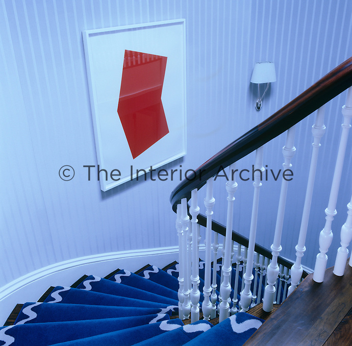 Looking down the curved staircase covered with a deep blue stair carpet
