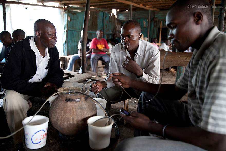 A group of Kenyans drink busaa, a traditional fermented beer, from a common pot using long straws - in a crowded busaa club at midday in a Nairobi slum on March 27, 2013. Busaa is made by crudely fermenting maize, millet, sorghum or molasses. At Kshs 35 per liter it is much cheaper than a Kshs120 half-liter bottle of commercial beer. The local brew was legalised in 2010 and since then busaa clubs have become increasingly popular. Drinking is on the rise in Kenya, especially among young people. Photo: Benedicte Desrus