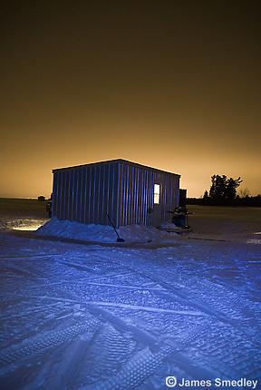 Ice fishing hut on frozen lake at night