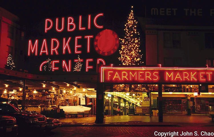 Red lighting from neon signage and Christmas fixtures color an empty Pike Place Market at night. Seattle, Washington State.