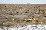 Brown choppy sea carrying sediment in suspension with distant container ship, North Sea, Suffolk, England