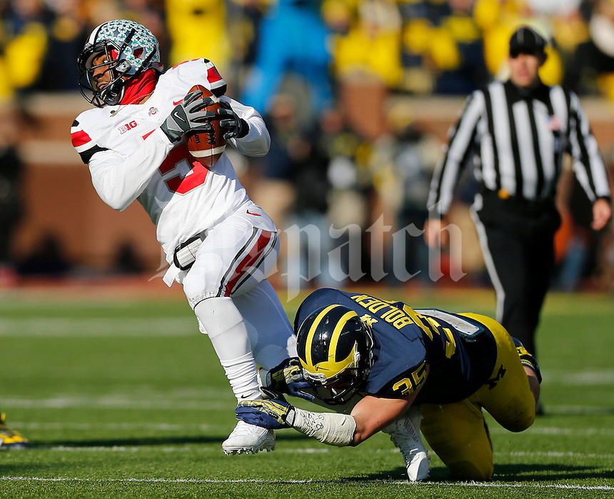 Michigan Wolverines linebacker Joe Bolden (35) brings down Ohio State Buckeyes quarterback Braxton Miller (5) during the first half of the NCAA football game at Michigan Stadium in Ann Arbor, Michigan on Saturday, November 30, 2013. (Columbus Dispatch photo by Jonathan Quilter)