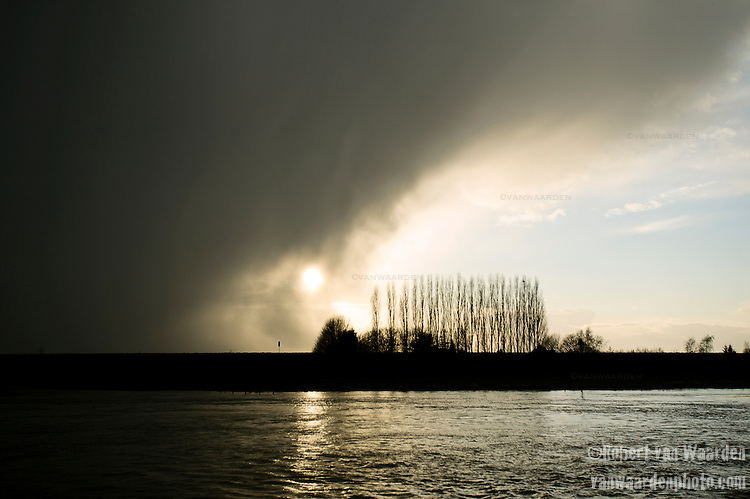 The sun falls behind a rain cloud over the Rhine river in the Netherlands.
