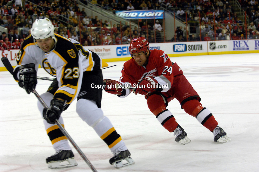 Carolina Hurricanes' Scott Walker (24) reaches at the Boston Bruins' Paul Mara (23) Saturday, Feb. 3, 2007 at the RBC Center in Raleigh. Boston won 4-3 in overtime.