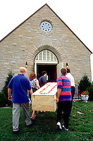 Pallbearers age 32 carrying plywood casket into church for funeral service.  Cambria Wisconsin USA