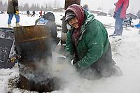 Volunteer/Nikolai resident Daryl Petruska stokes fire to keep mushers water hot @ Nikolai Chkpt 2006 Iditarod Alaska Winter