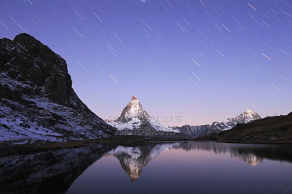 Matterhorn at night with star trails in winter with reflection in the Riffelsee, Zermatt, Valais, Switzerland, Europe