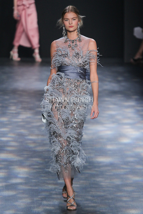 Model Kate walks runway in a dusty blue ostrich feather cocktail with gunmetal embroidery and satin-faced organza sash, from the Marchesa Fall 2016 collection by Georgina Chapman and Keren Craig, presented at NYFW: The Shows Fall 2016, during New York Fashion Week Fall 2016.