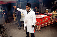 A Uighur man tries to attract people to his small restaurant in the Grand Bazaar in Kashgar, Xinjiang, China.