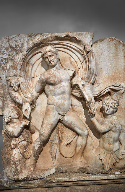 Close up of a Roman Sebasteion relief  sculpture of Emperor Claudius as God of sea and land,  Aphrodisias Museum, Aphrodisias, Turkey.  Against a grey background.<br /> <br /> The Emperor as god Claudius strides forward in a divine epiphany, drapery billowing around his head. He receives a cornucopia with fruits of the earth from a figure emerging from the ground, anda ship's steering oar from a marine tritoness with fish legs. The idea is clear: the god-emperor guarantees the prosperity of land and sea. The relief is a remarkable local visualisation - elevated and panegyrical - of the emperor's role as a universal saviour and divine protector.