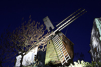 PARIS, FRANCE - JANUARY 20: A low angle view of Le Moulin de la Galette on January 20, 2009, in Montmartre, Paris, France. The windmill, seen in the blue light of an early morning in winter, is now a restaurant. Originally two windmills grinding flour for the city, it became a restaurant in 1870, and appears in paintings by Renoir and other artists. (Photo by Manuel Cohen)