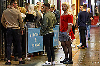 Pictured: A man in a Santa outfit in Wind Street, Swansea, Wales, UK. Friday 20 December 2019<br /> Re: Black Eye Friday (also known as Black Friday, Mad Friday, Frantic Friday) the last Friday before Christmas, in Swansea, Wales, UK.
