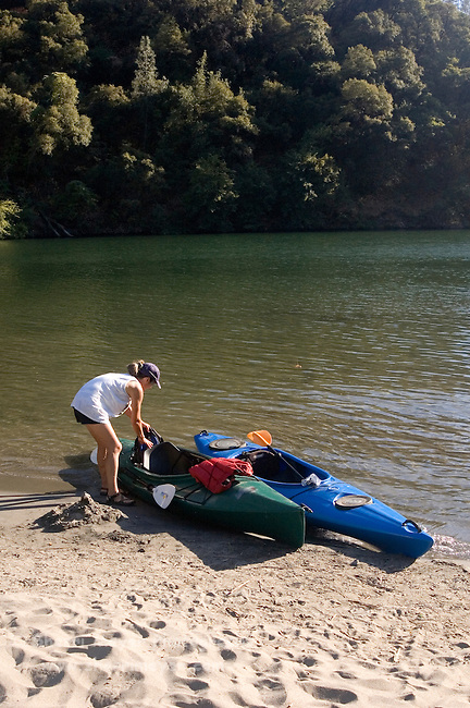 Woman unloading gear from kayaks at Lake Clementine