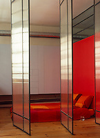 A bright red wall enhances the sense of privacy in this low-key bedroom separated from the living area by pivoting translucent panels