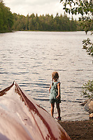 A young girl plays near the water and a red canoe at Craig Lake State Park near Michigamme Michigan.