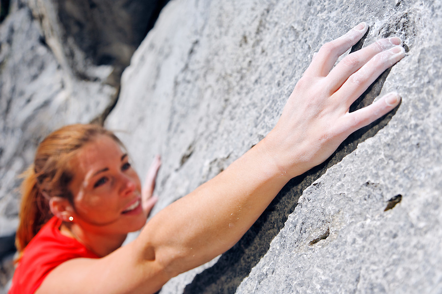 Female climber reaching for hold on rock face, Banff, Banff National Park, Alberta, Canada