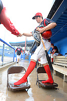 Batavia Muckdogs outfielder Connor Burke (16) gets some help across a bridge made of chairs after the dugout flooded during a brief but heavy rain storm during a game against the Hudson Valley Renegades on August 8, 2013 at Dwyer Stadium in Batavia, New York.   The game was called due to unplayable field conditions.  (Mike Janes/Four Seam Images)