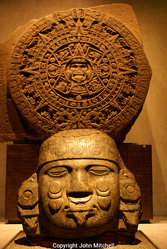 Aztec sculpture with Aztec calendar stone or Sun Stone in background, Sala Mexica, National Museum of Anthropolgy or Museo Nacional de Antropologia in Chapultepec Park, Mexico City.